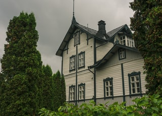 white and black house near green trees under white clouds during daytime