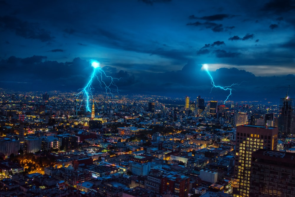 city with high rise buildings under blue sky with lightning during nighttime