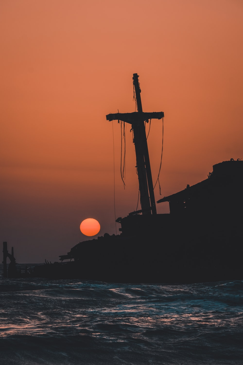 silhouette of ship on sea during sunset