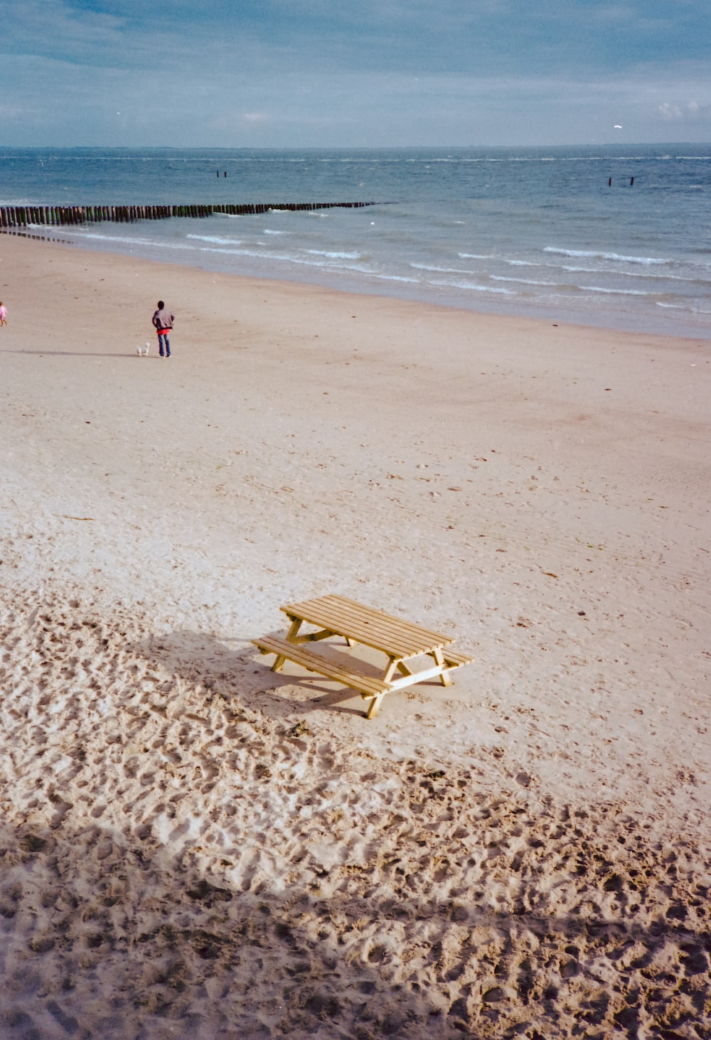 brown wooden lounge chair on beach during daytime