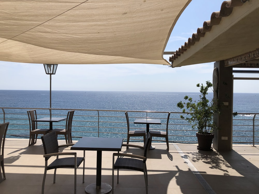 brown wooden table and chairs near sea during daytime