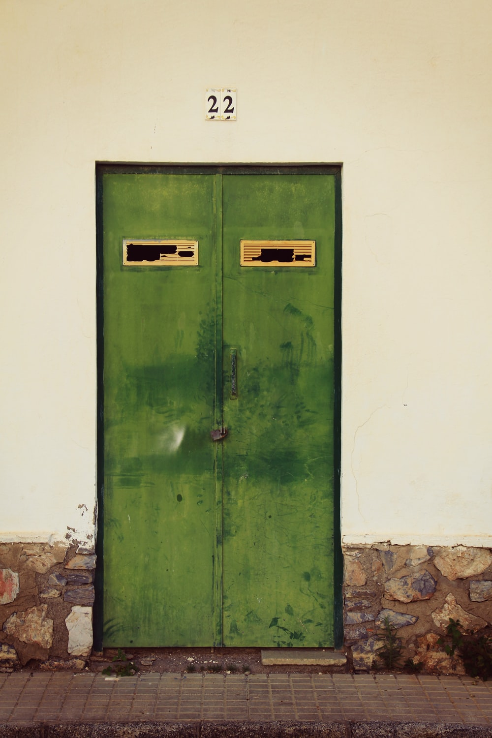 green wooden door on white painted wall