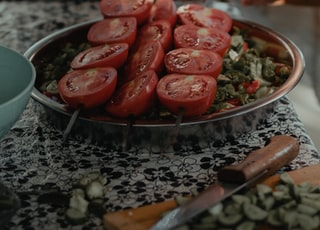 red sliced tomatoes on stainless steel round tray