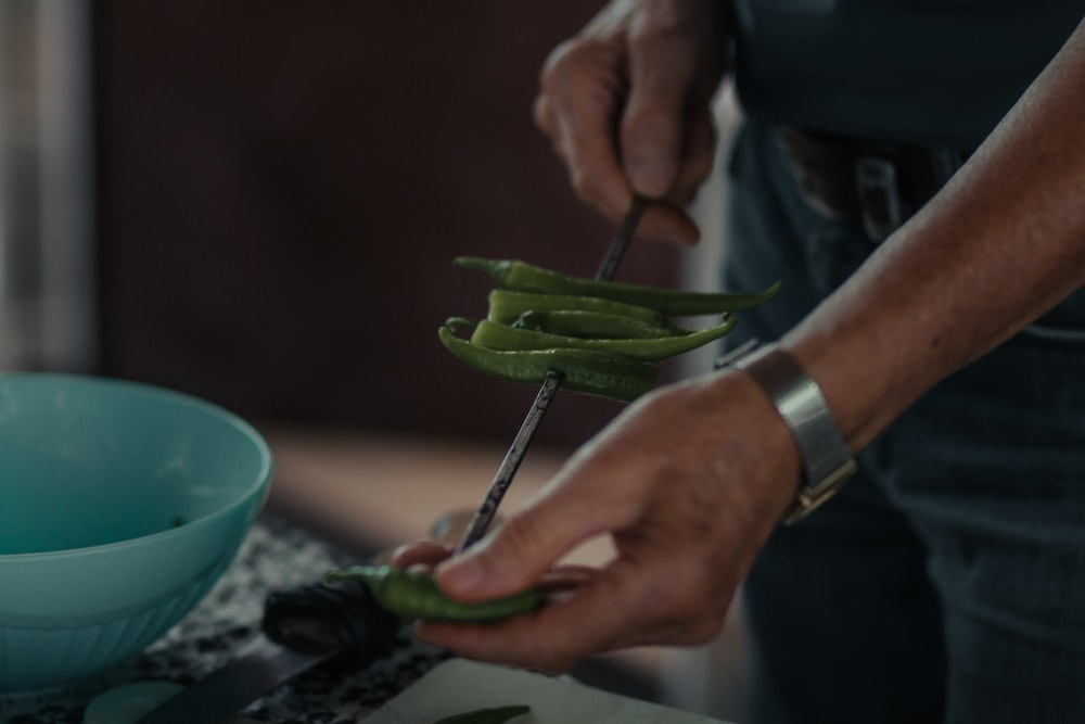 person holding green vegetable on green ceramic plate