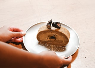 person holding white ceramic plate with brown and black food