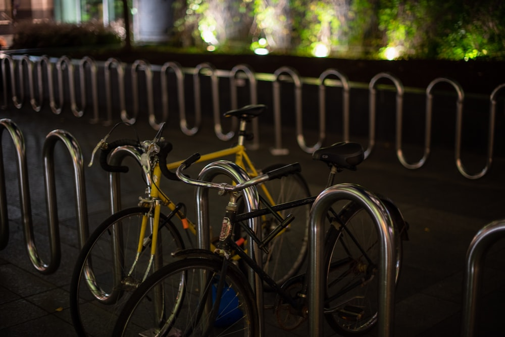 black bicycle leaning on gray metal fence during daytime