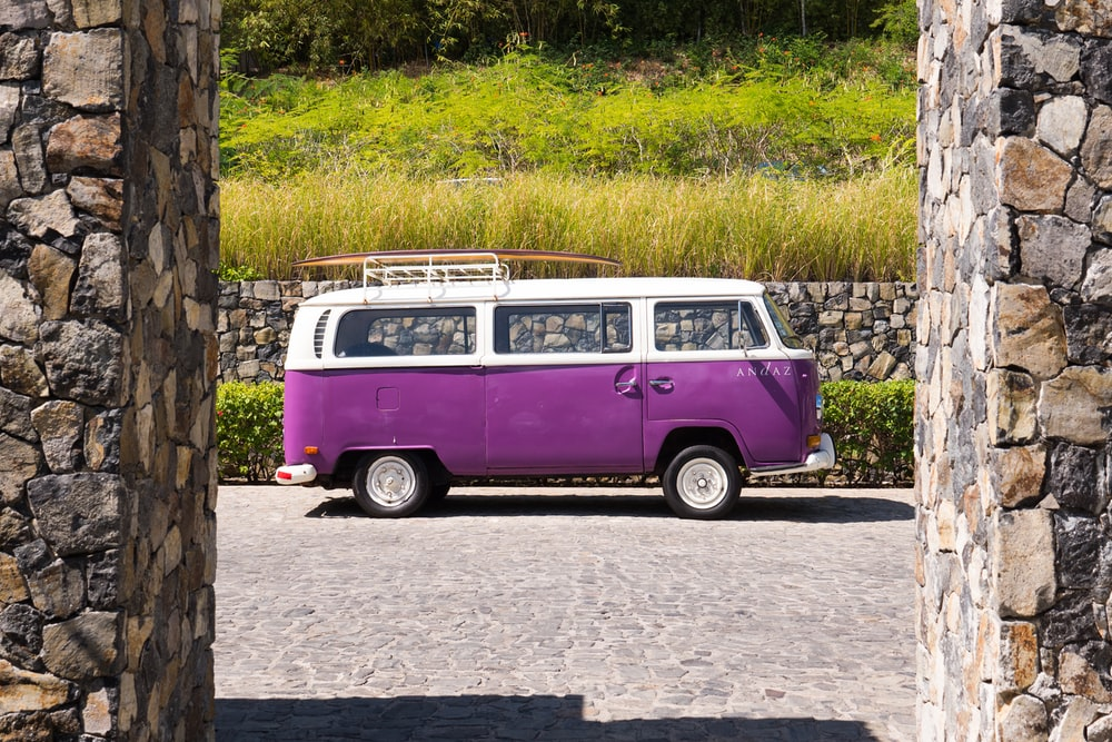 purple and white volkswagen t-2 on gray concrete road during daytime