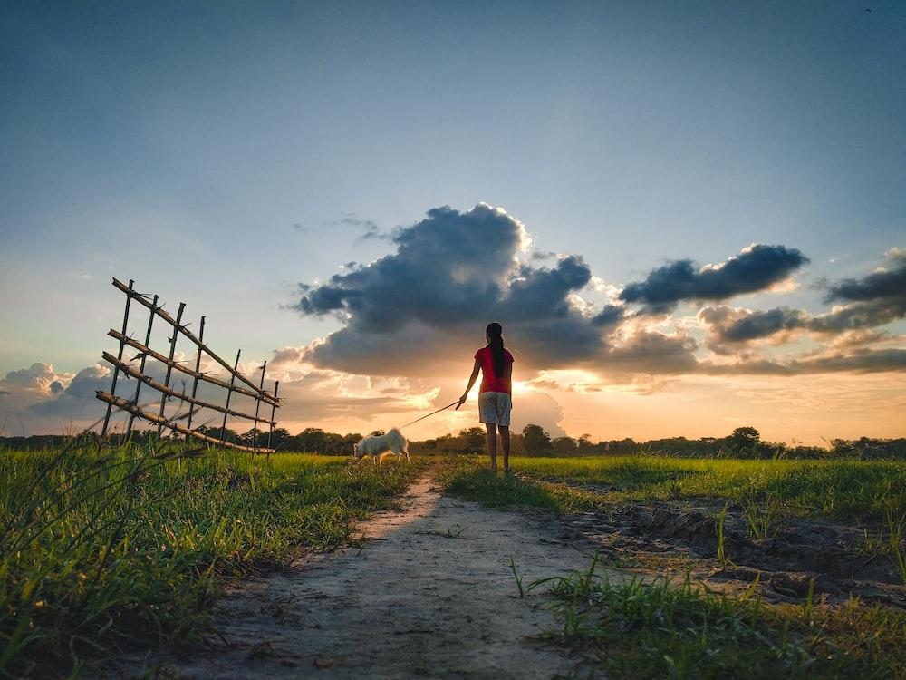 man in red shirt walking on dirt road during daytime