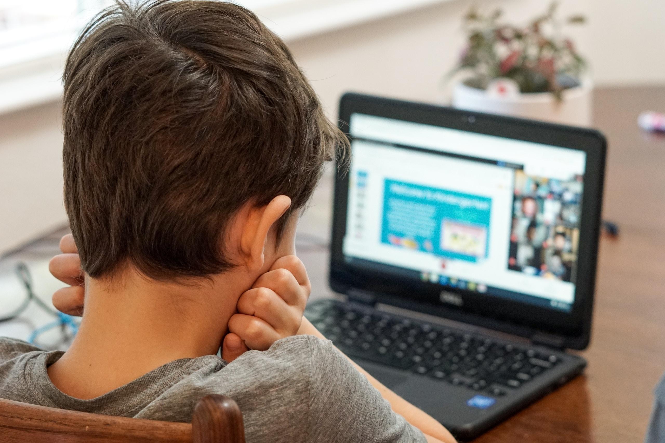 boy in gray shirt using black laptop computer