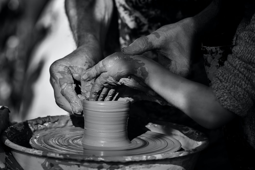 person making clay pot on round clay pot