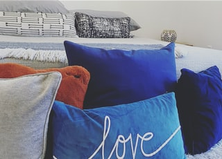 blue and white throw pillows on gray couch