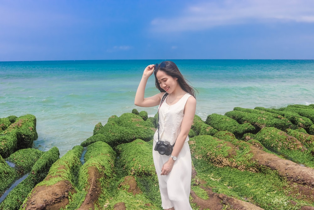 woman in white dress standing on green grass near body of water during daytime
