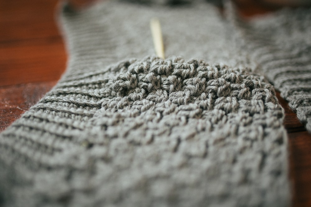 person holding gray knit textile