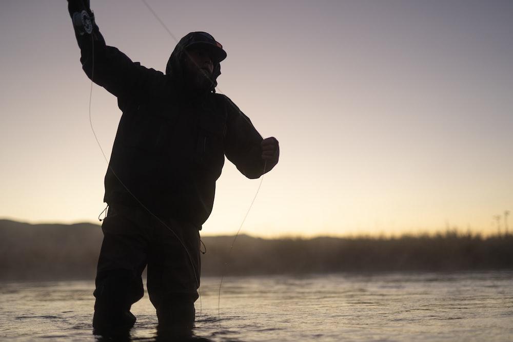 man in black jacket and brown pants fishing during daytime