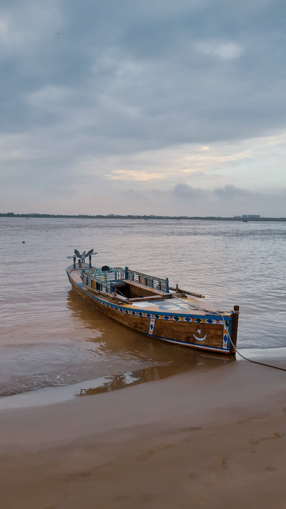 brown and white boat on sea shore during daytime