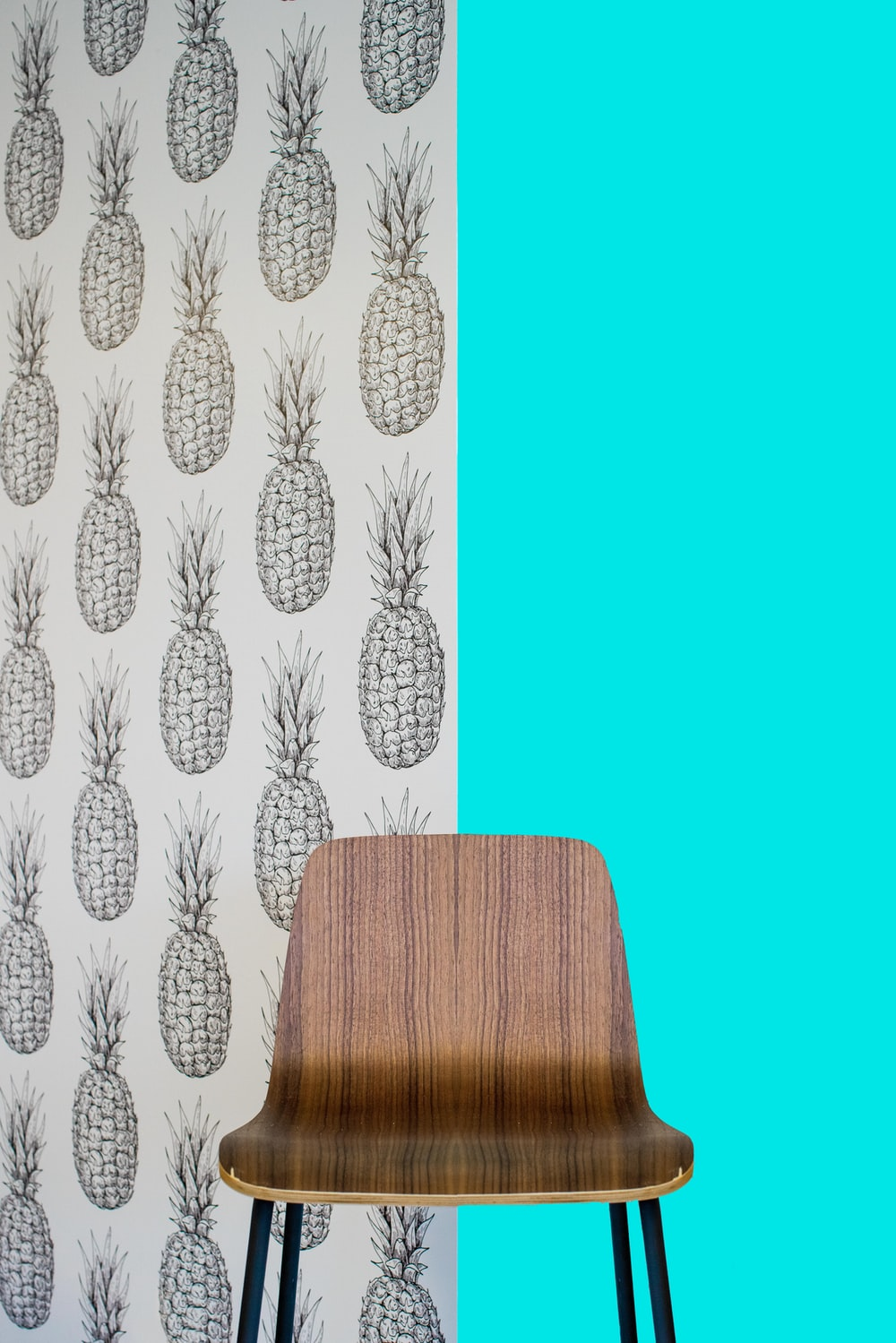 brown wooden seat beside white and blue floral wall