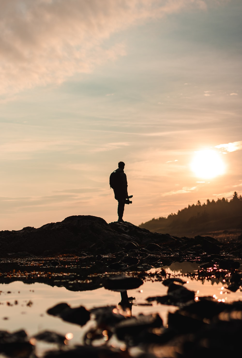 silhouette of man standing on rock formation during sunset