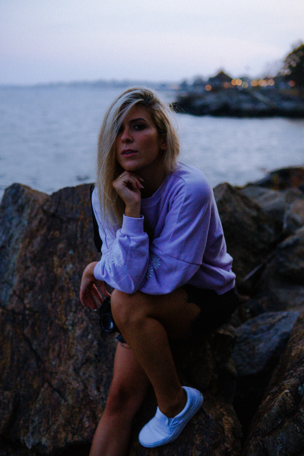 woman in purple long sleeve shirt sitting on rock near body of water during daytime