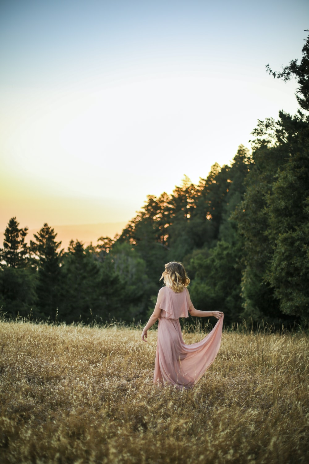 woman in pink dress standing on brown grass field during daytime