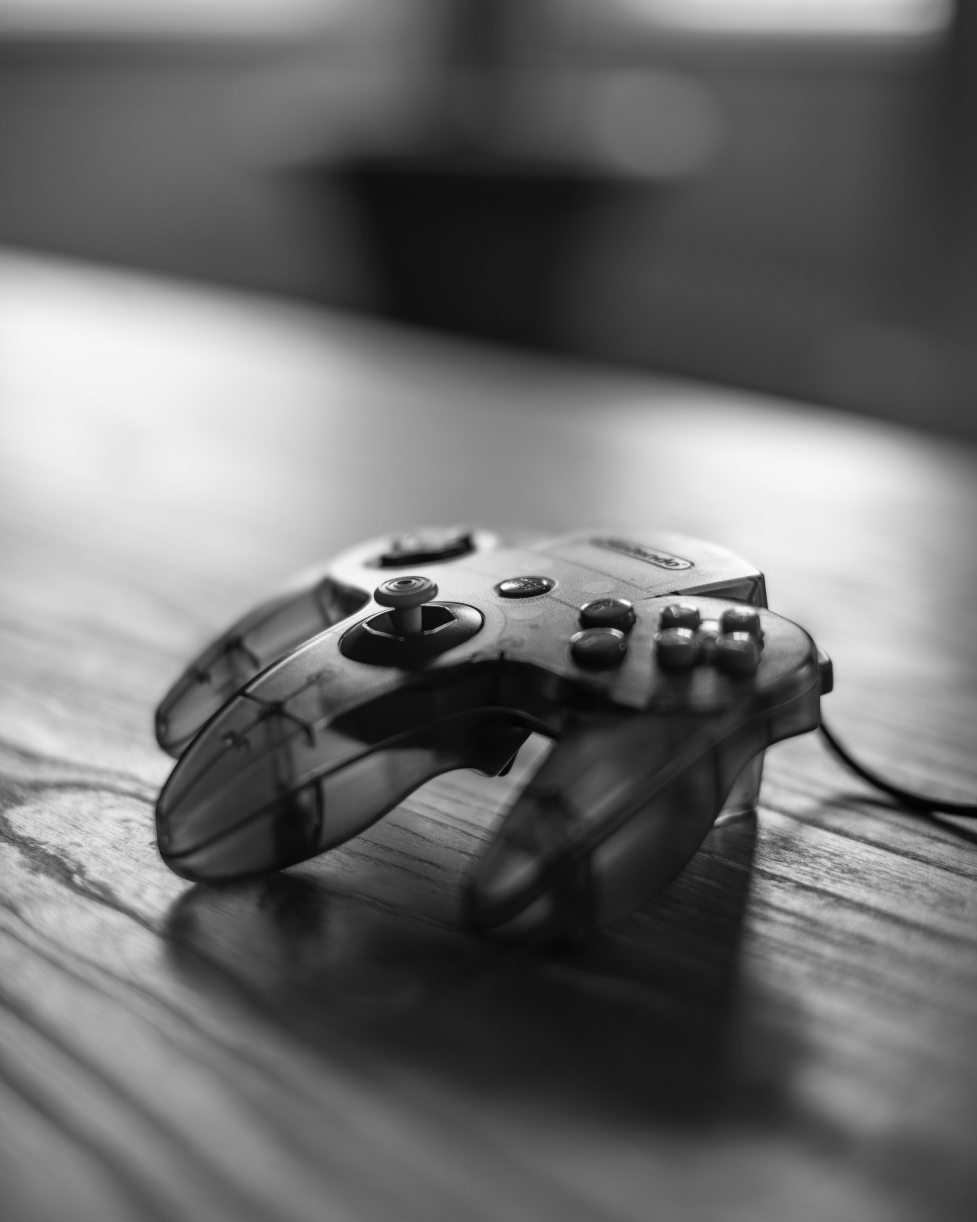 A closeup of a three-pronged, see-through Nintendo 64 controller, in black-and-white.