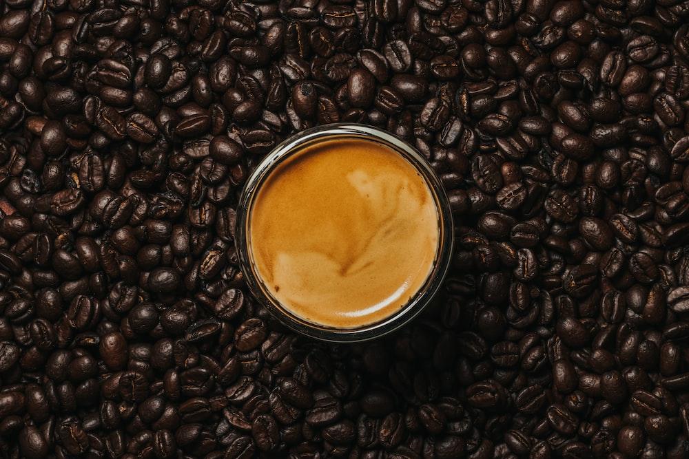 black coffee beans on white ceramic mug