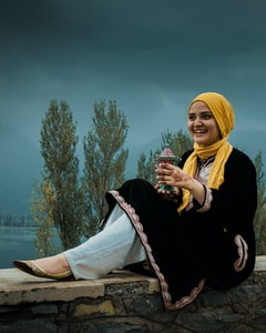 woman in black jacket and white hijab sitting on brown wooden log during daytime
