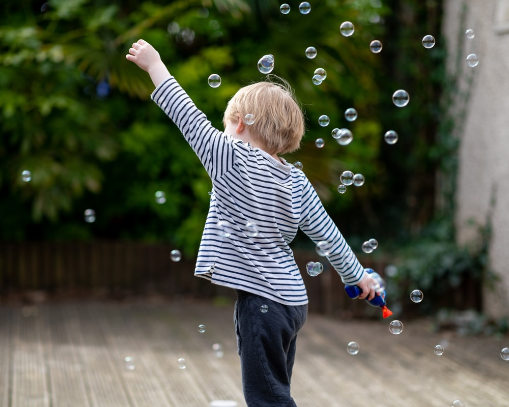 child in black and white striped long sleeve shirt playing bubbles