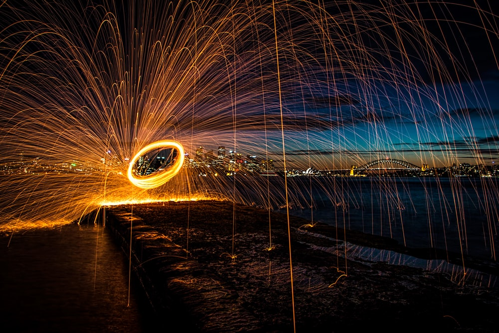 steel wool photography of person standing on bridge