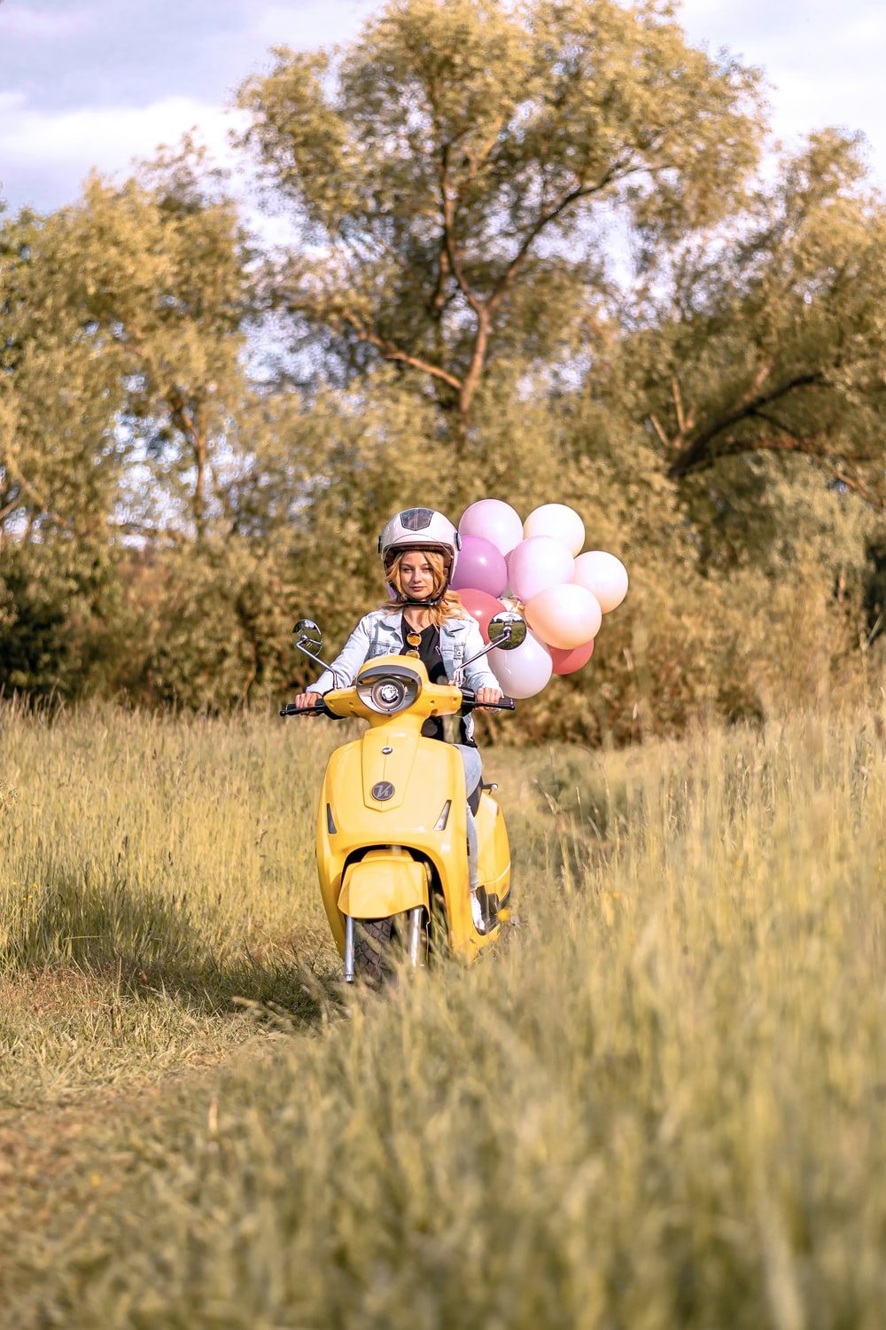 white and pink balloons on yellow motor scooter