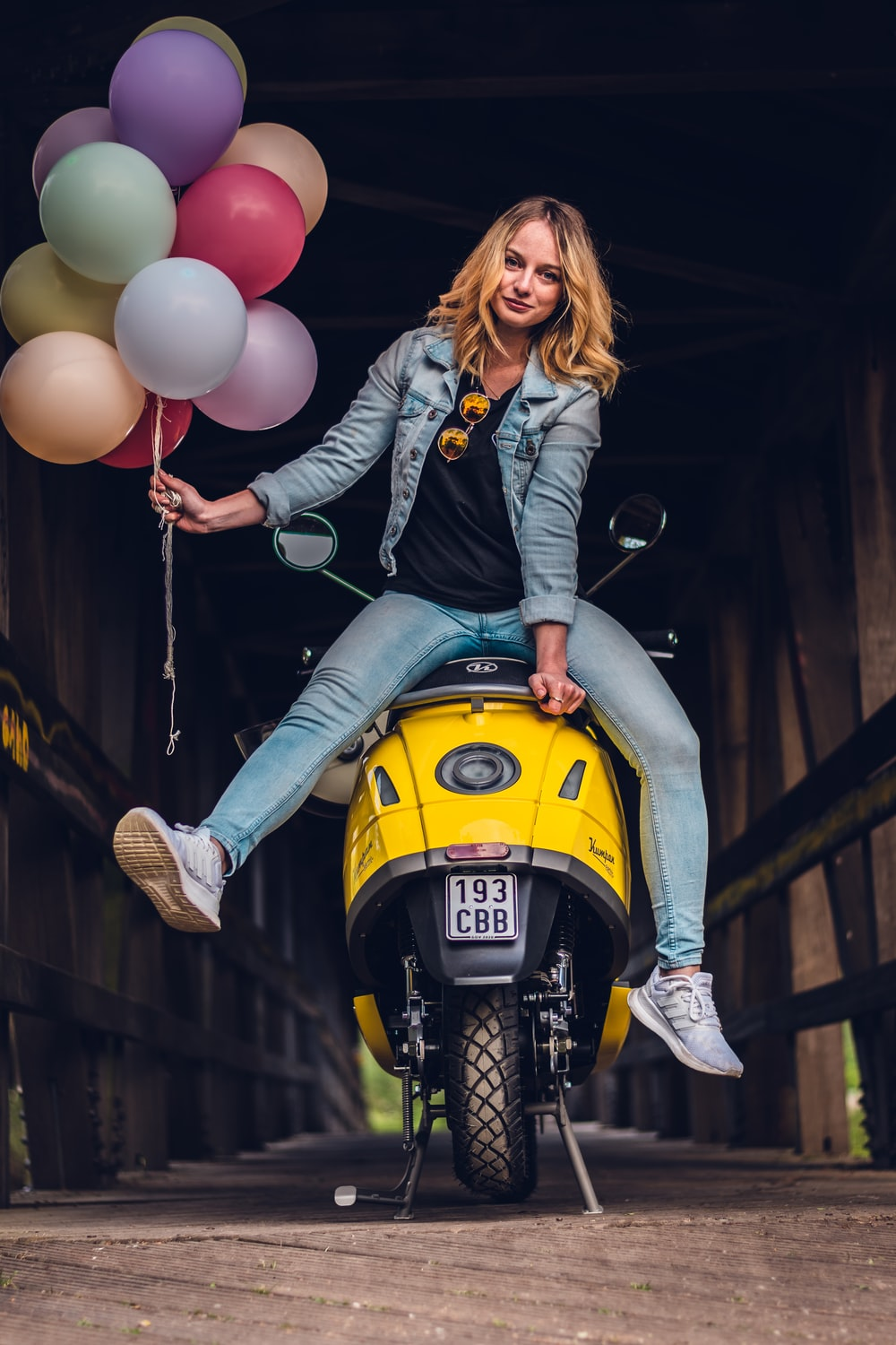 woman in black leather jacket and blue denim jeans riding yellow motorcycle holding balloons