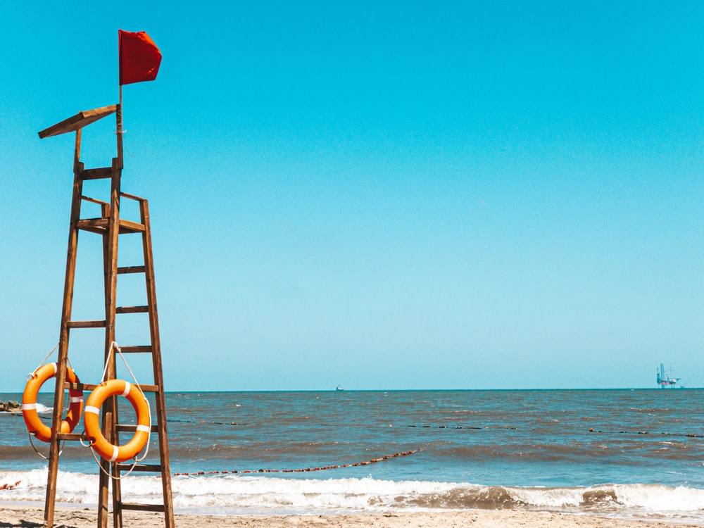 red flag on brown wooden ladder on beach during daytime