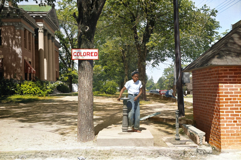 A young African American boy drinks out of a fountain labeled 'Colored'