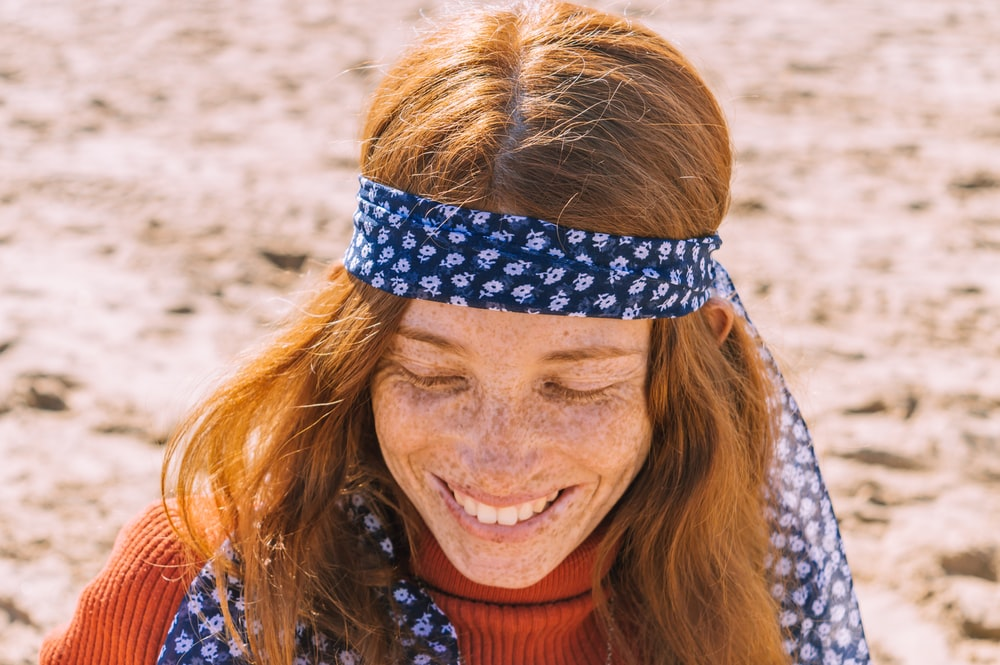 woman in orange shirt wearing blue and white head band