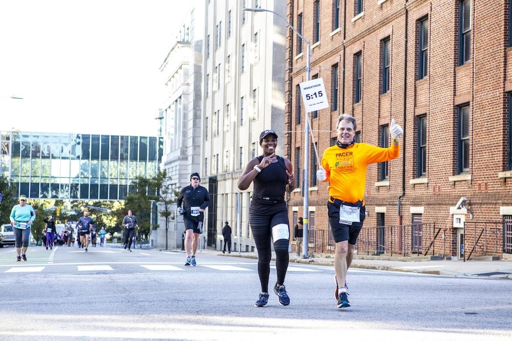 man in orange t-shirt and black shorts running on road during daytime