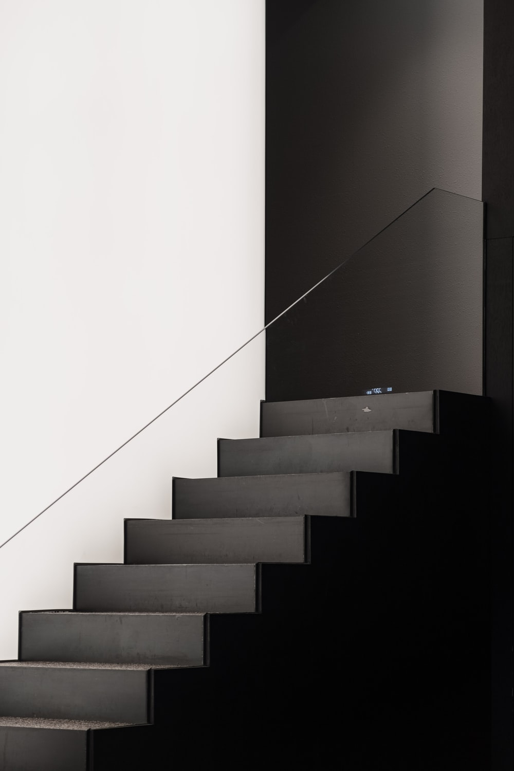black concrete staircase with white wall
