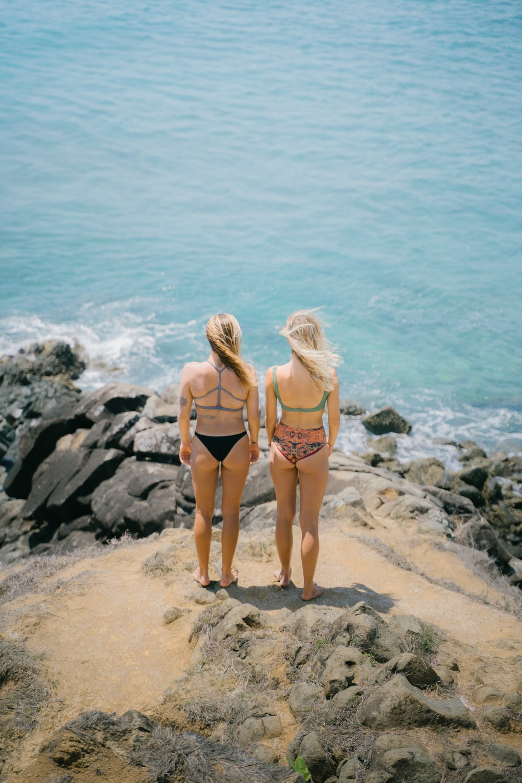 2 women in bikini standing on rocky shore during daytime