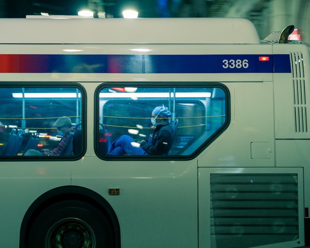 man in black jacket sitting on white bus