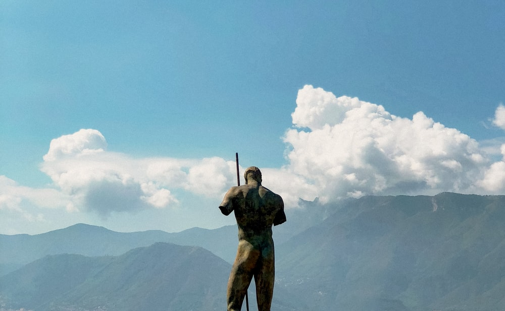 man in green and black camouflage jacket holding rifle standing on rock formation under blue sky