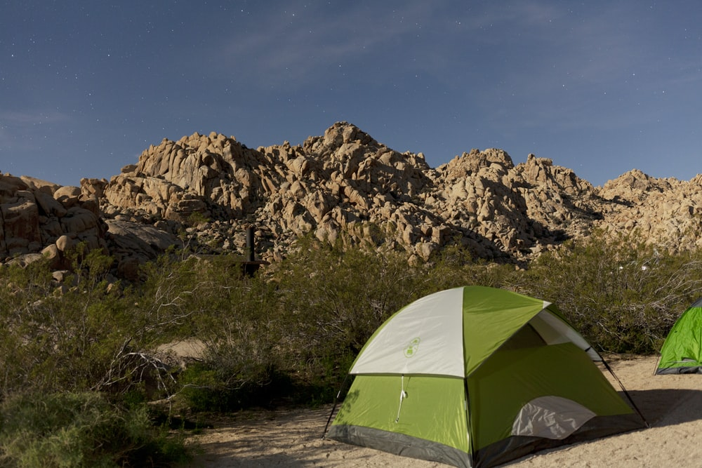 green dome tent on brown rock mountain during daytime