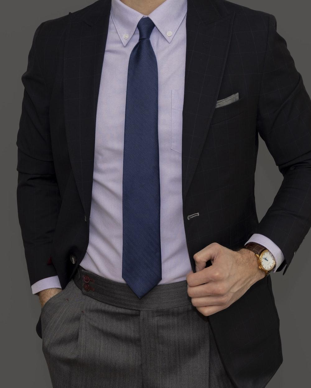 man in black suit jacket and blue necktie