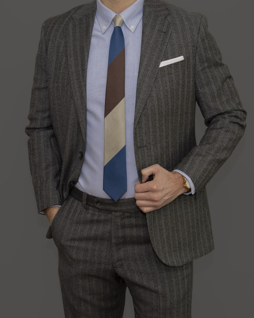 man in gray suit jacket and blue necktie