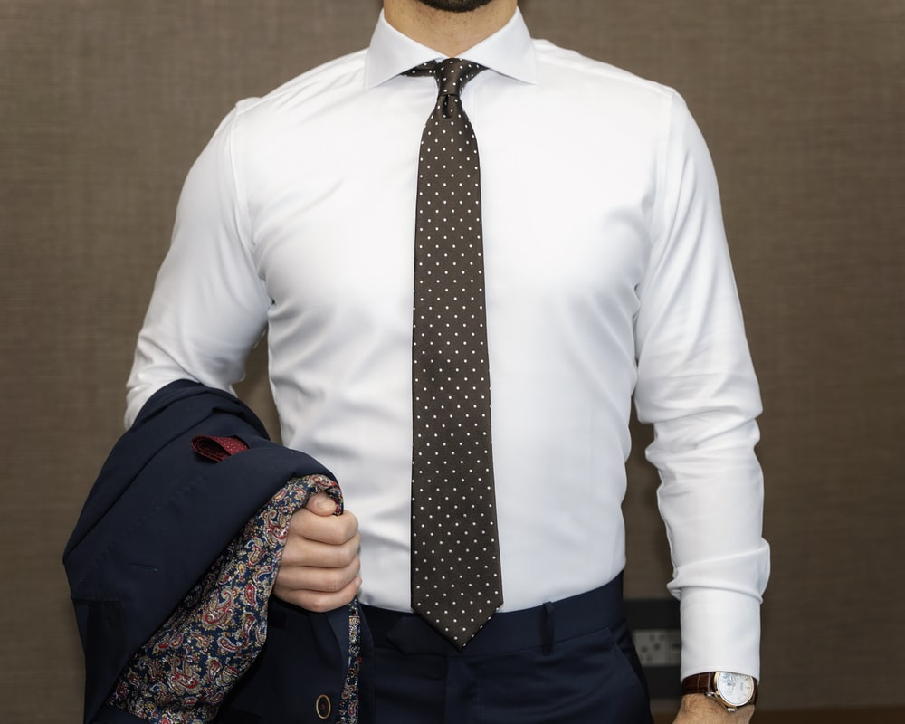man in white dress shirt with black and white polka dots necktie