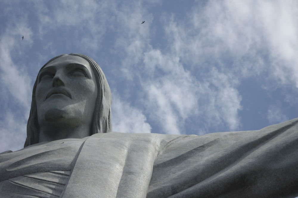 low angle photography of statue of man under blue sky during daytime