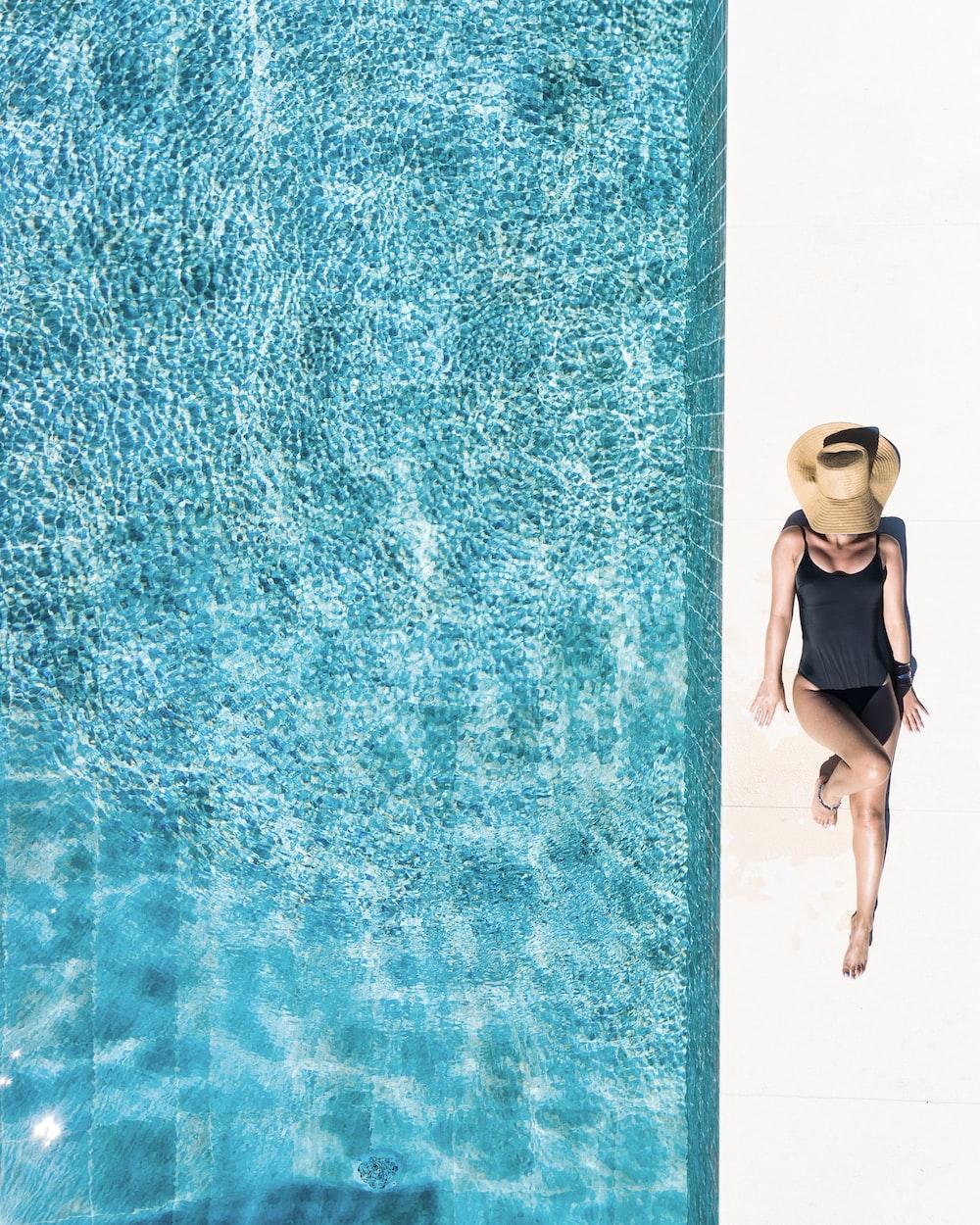 woman in black bikini bottom and white sun hat standing on blue water