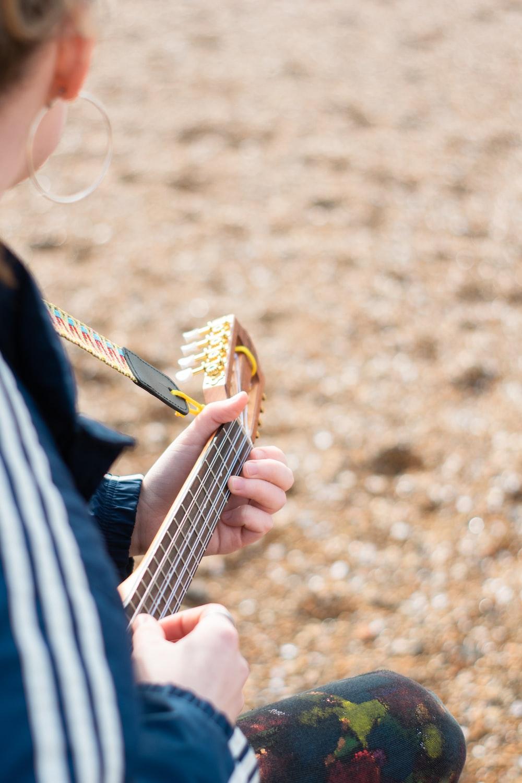 person playing guitar during daytime