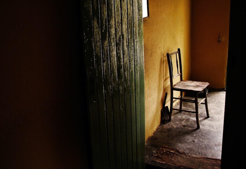 brown wooden armchair beside gray steel wall