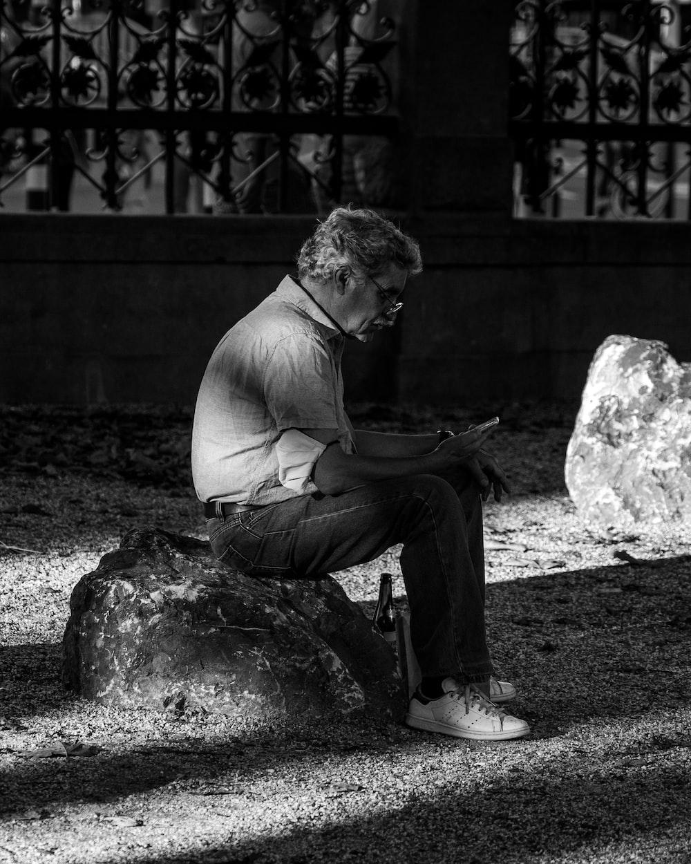 man in white crew neck t-shirt sitting on rock