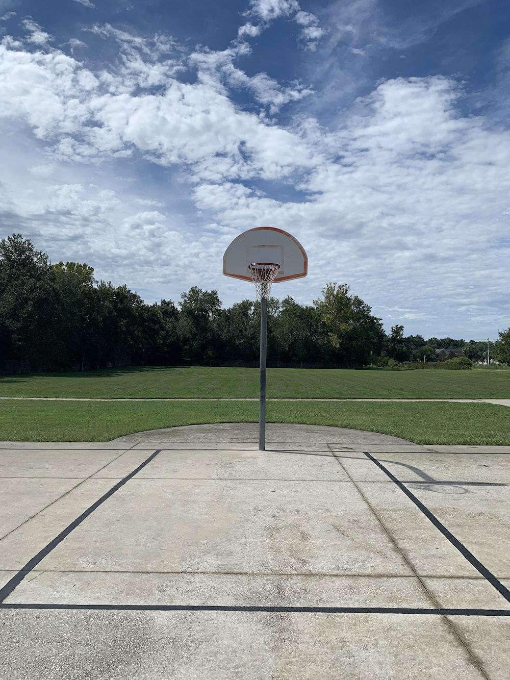 basketball hoop on green grass field under blue sky during daytime