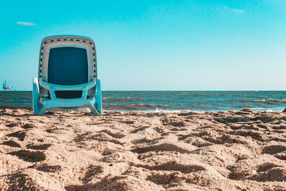 blue and white plastic chair on beach during daytime