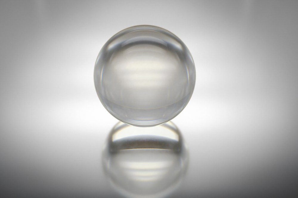 clear glass ball on white surface